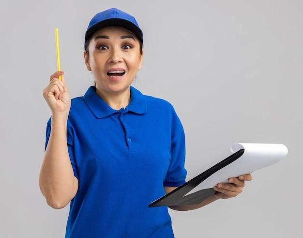 Jonge bezorger in blauw uniform en pet met klembord en pen blij en verrast