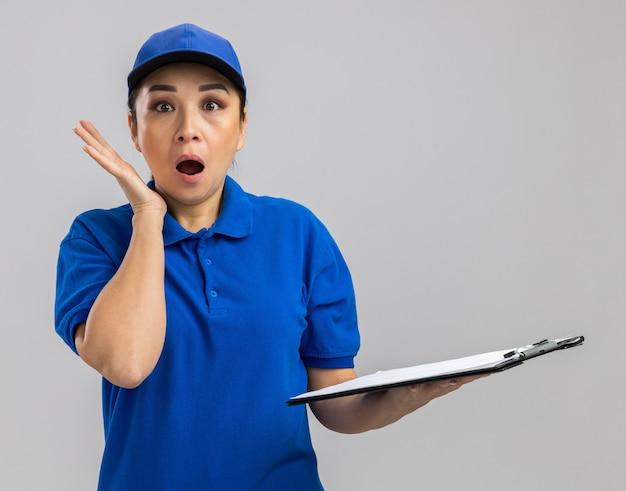 Jonge bezorger in blauw uniform en pet met klembord en pen verbaasd en verrast
