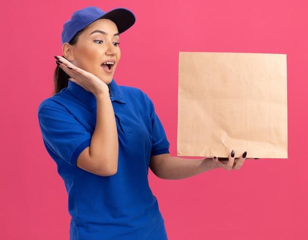 Jonge bezorger in blauw uniform en pet met papieren pakket kijkend naar het verbaasd en verrast staande over roze muur Gratis Foto