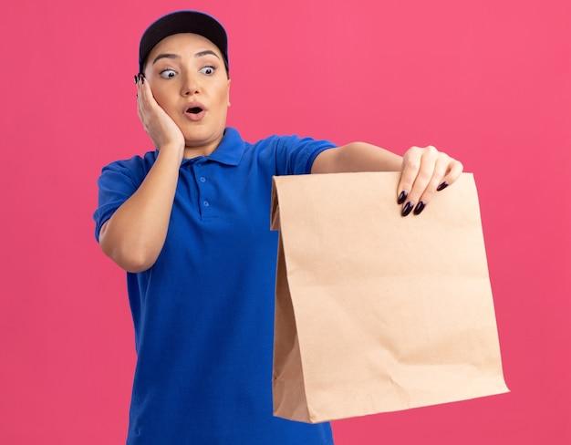 Jonge bezorger in blauw uniform en pet met papieren pakket kijkend naar het, verbaasd en verrast staande over roze muur Gratis Foto