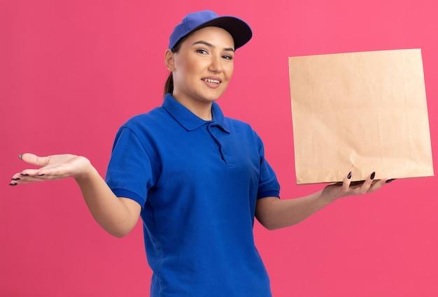 Jonge bezorger in blauw uniform en pet met papieren pakket kijkend naar voorkant lachend met blij gezicht presenteren met arm van haar hand staande over roze muur