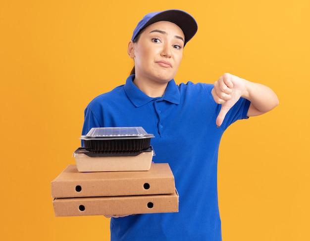 Jonge bezorger in blauw uniform en pet met pizzadozen en voedselpakketten kijken naar voorkant verward en ontevreden met duimen naar beneden staande over oranje muur