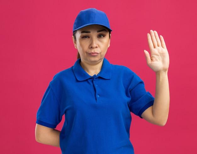 Jonge bezorger in blauw uniform en pet met serieus gezicht dat hand opsteekt over roze muur