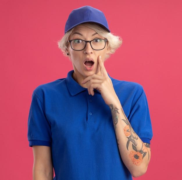 Jonge bezorger in blauw uniform en pet verrast en verbaasd met wijd open mond over roze muur