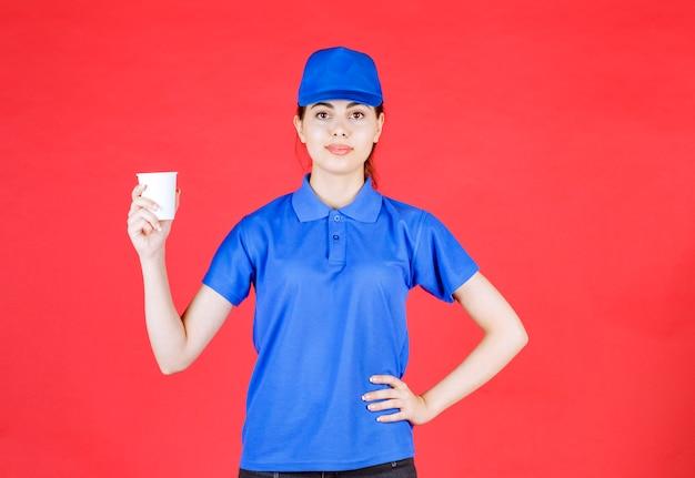 Jonge bezorger in blauwe dop poseren met plastic kopje thee op rood.