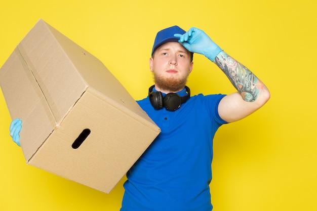 Jonge bezorger in blauwe polo blauwe pet witte jeans rugzak met een doos op geel