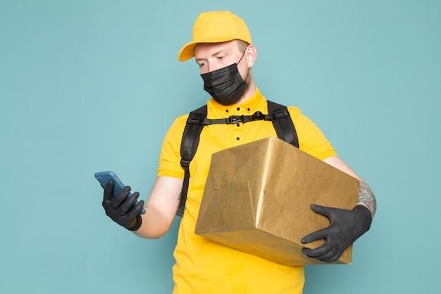 Jonge bezorger in gele polo gele pet witte jeans rugzak en zwart steriel masker met een doos op blauw