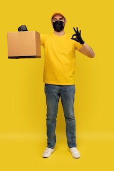Jonge bezorger in gele t-shirt, masker, handschoenen