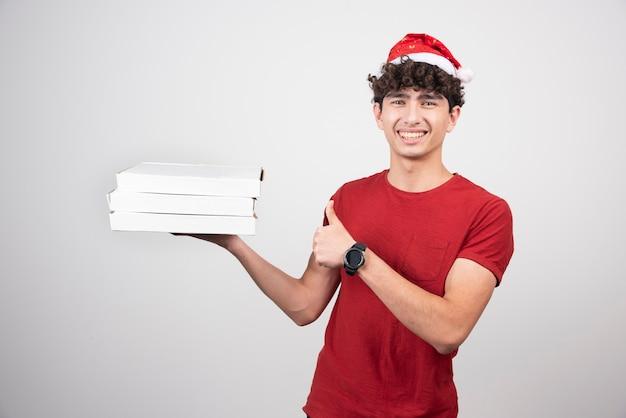 Jonge bezorger in kerstmuts die duimen opgeeft.