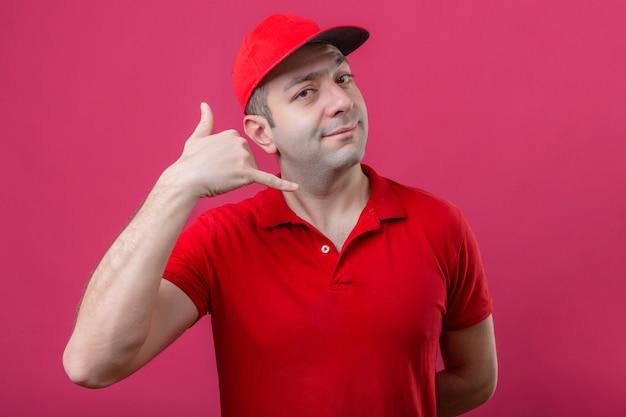 Jonge bezorger in rood poloshirt en pet die bel me gebaar maken op zoek overtuigd en zelfverzekerd over geïsoleerde roze achtergrond