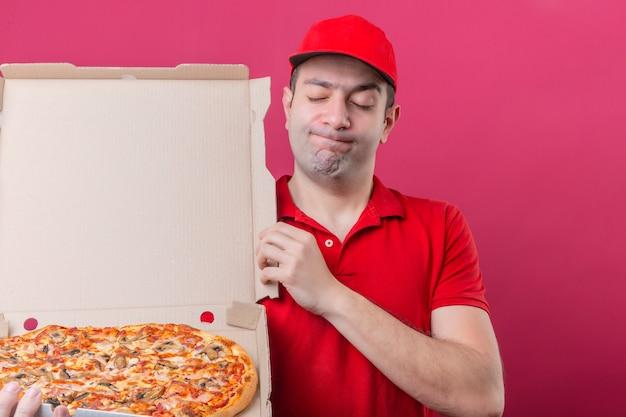Jonge bezorger in rood poloshirt en pet die zich met doos van verse pizza ontevreden sluitende ogen over geïsoleerde roze achtergrond bevinden