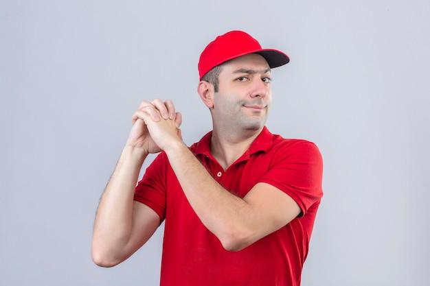 Jonge bezorger in rood poloshirt en pet die zich met een gebaar van groepswerk over geïsoleerde witte achtergrond bevinden