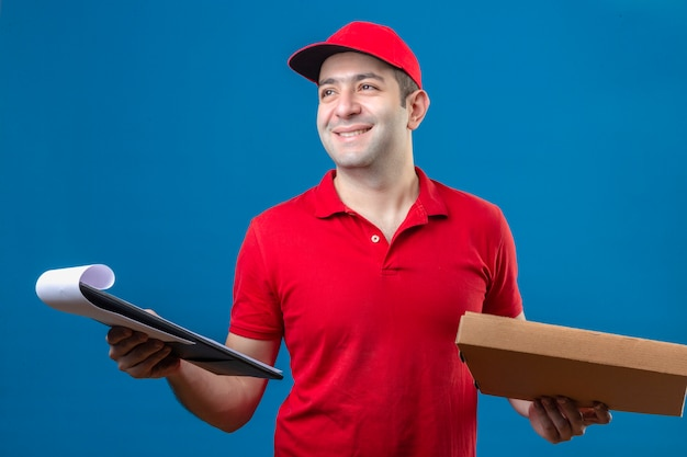 Jonge bezorger in rood poloshirt en pet permanent met pizzadoos en klembord in handen glimlachend vriendelijk met blij gezicht over geïsoleerde blauwe achtergrond