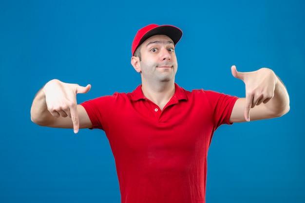 Jonge bezorger in rood poloshirt en pet wijzend met vinger naar beneden kijken camera met glimlach tevreden uitdrukking over geïsoleerde blauwe achtergrond