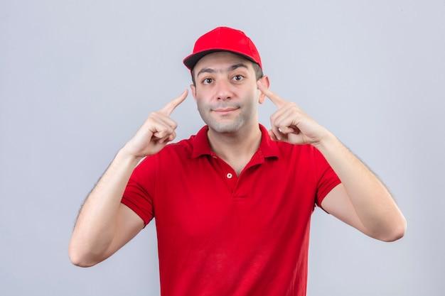 Jonge bezorger in rood poloshirt en pet wijzend naar zijn ogen glimlachend staande over geïsoleerde witte achtergrond