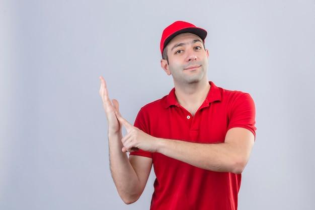 Jonge bezorger in rood poloshirt en pet wijzende wijsvinger naar palm op zoek zelfverzekerd over geïsoleerde witte achtergrond