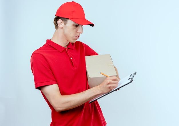Jonge bezorger in rood uniform en glb bedrijf doos pakket en klembord iets schrijven met ernstig gezicht staande over witte muur