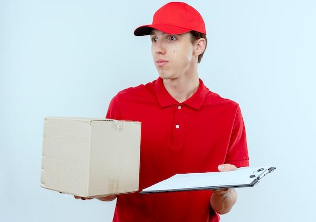 Jonge bezorger in rood uniform en glb bedrijf doos pakket en klembord opzij kijken verbaasd staande over witte muur