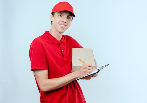 Jonge bezorger in rood uniform en glb bedrijf doos pakket en klembord schrijven iets glimlachen naar de voorkant staande over witte muur