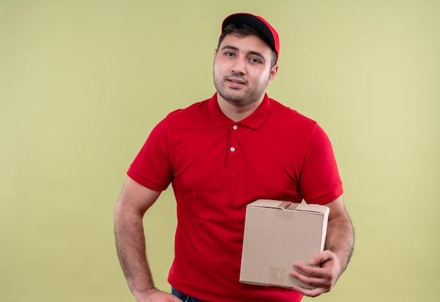 Jonge bezorger in rood uniform en glb bedrijf doos pakket glimlachend vriendelijk staande over groene muur