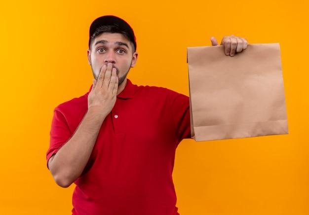 Jonge bezorger in rood uniform en glb die document pakket houden dat verbaasd kijkt die mond met hand bedekt
