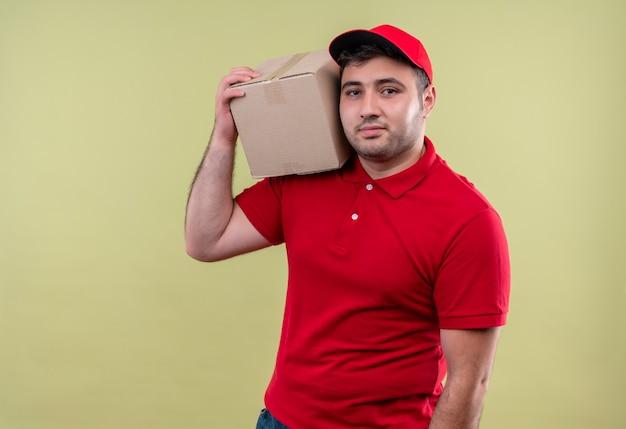 Jonge bezorger in rood uniform en glb holding box pakket glimlachend zelfverzekerd staande over groene muur