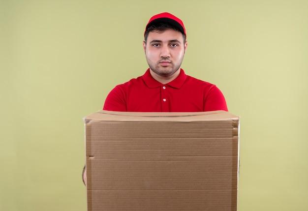 Jonge bezorger in rood uniform en glb met doos pakket met ernstig gezicht staande over groene muur