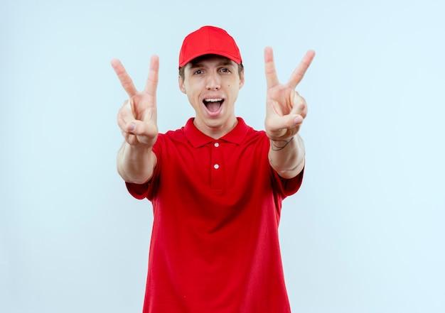 Jonge bezorger in rood uniform en pet blij en opgewonden met overwinningsteken met beide handen staande over witte muur