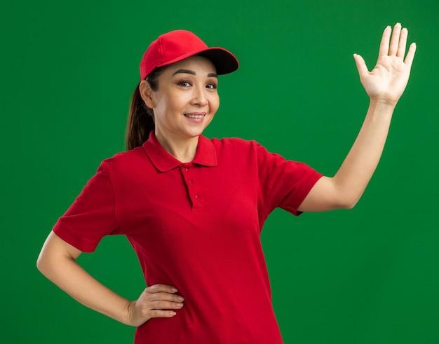 Jonge bezorger in rood uniform en pet, blij en positief, opgestoken hand glimlachend vrolijk over groene muur staand