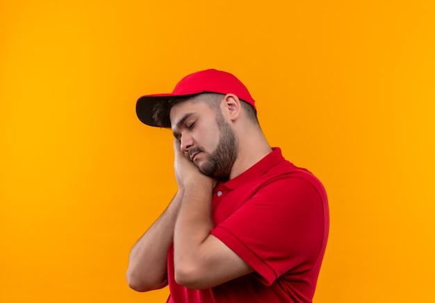 Jonge bezorger in rood uniform en pet die de handpalmen tegen elkaar houdt, hoofd op de handpalmen leunt, wil moe en overwerkt slapen