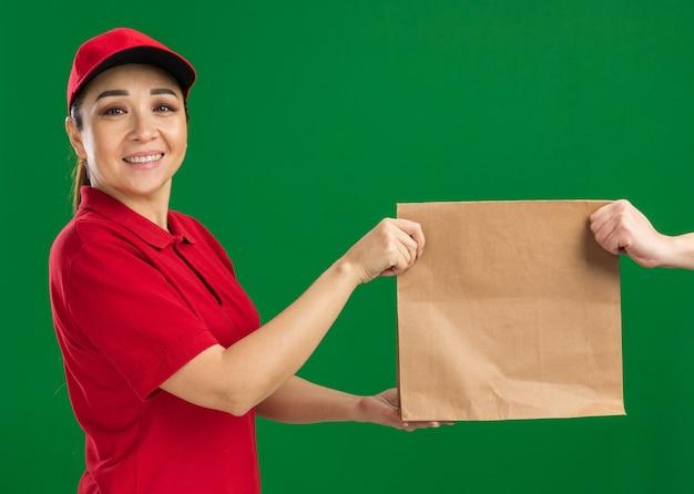 Jonge bezorger in rood uniform en pet die een papieren pakket geeft aan een klant die zelfverzekerd glimlacht en over de groene muur staat