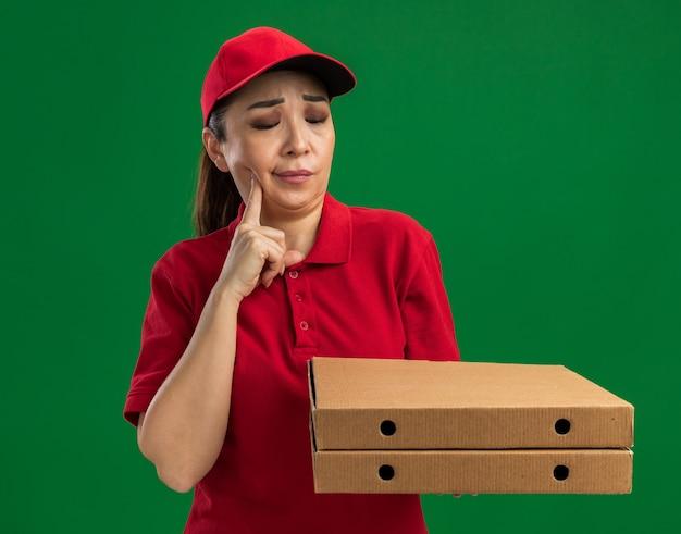 Jonge bezorger in rood uniform en pet die pizzadozen vasthoudt en kijkt hoe ze in de war zijn