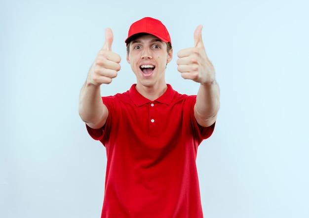 Jonge bezorger in rood uniform en pet glimlachend blij en positief duimen opdagen staande over witte muur