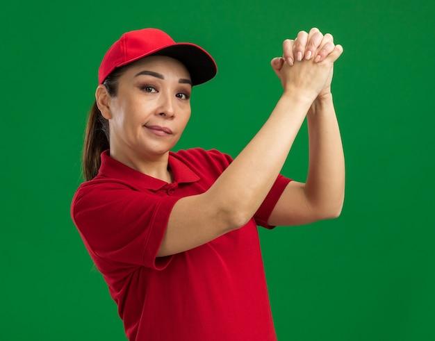 Jonge bezorger in rood uniform en pet hand in hand en maakt teamwerkgebaar met zelfverzekerde uitdrukking die over groene muur staat