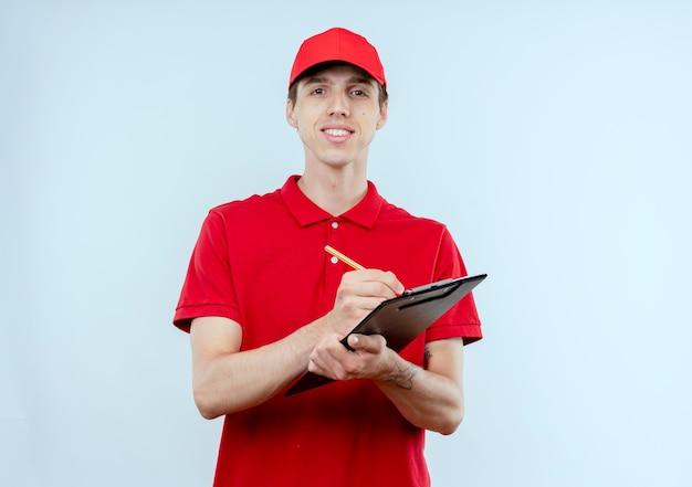 Jonge bezorger in rood uniform en pet houden en pencile naar de voorkant kijken met zelfverzekerde uitdrukking staande over witte muur
