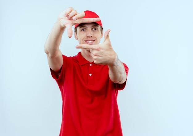 Jonge bezorger in rood uniform en pet maken frame met vingers glimlachend naar voren kijkend door dit frame staande over witte muur