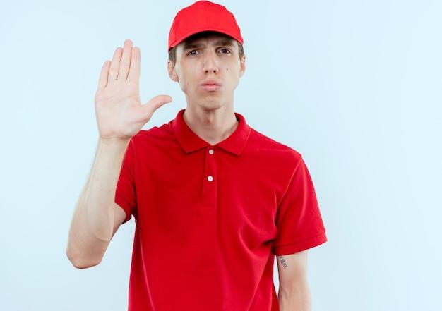 Jonge bezorger in rood uniform en pet maken stopbord met open hand kijkend naar de voorkant met ernstig gezicht staande over witte muur