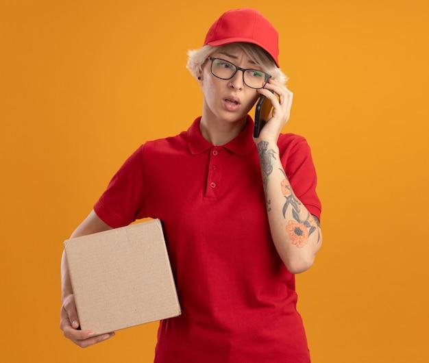Jonge bezorger in rood uniform en pet met bril met kartonnen doos praten op mobiele telefoon verward en zeer angstig staande over oranje muur