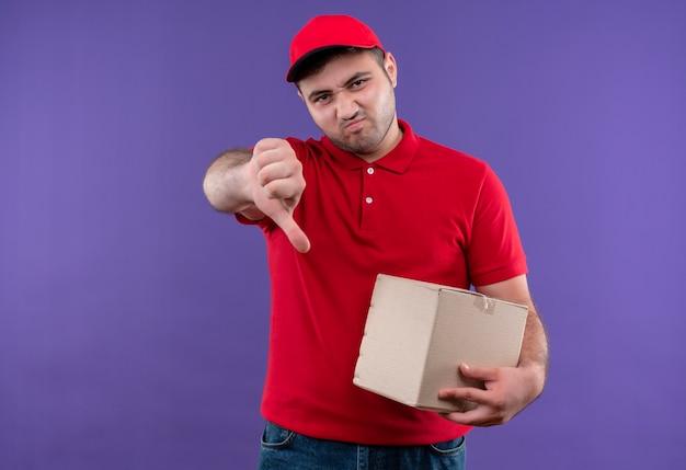 Jonge bezorger in rood uniform en pet met doos pakket, duimen naar beneden met fronsend gezicht staande over paarse muur