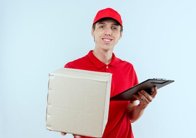 Jonge bezorger in rood uniform en pet met doos pakket en klembord op zoek naar de voorkant glimlachend staande over witte muur