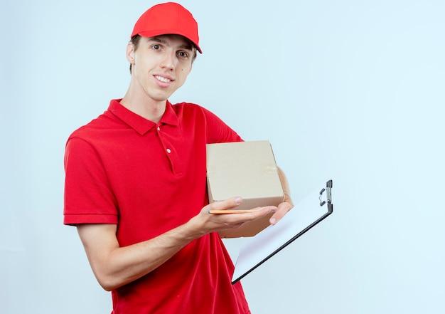 Jonge bezorger in rood uniform en pet met doos pakket en klembord op zoek naar de voorkant glimlachend zelfverzekerd staande over witte muur