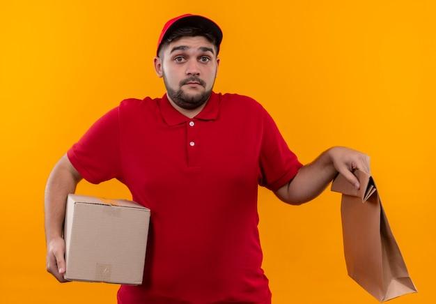 Jonge bezorger in rood uniform en pet met doos pakket en papieren zak op zoek verward en onzeker