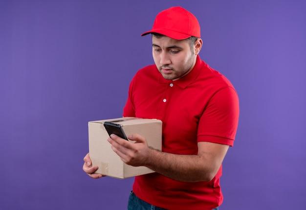 Jonge bezorger in rood uniform en pet met doos pakket kijken naar het scherm van zijn smartphone kijkend verward staande over paarse muur