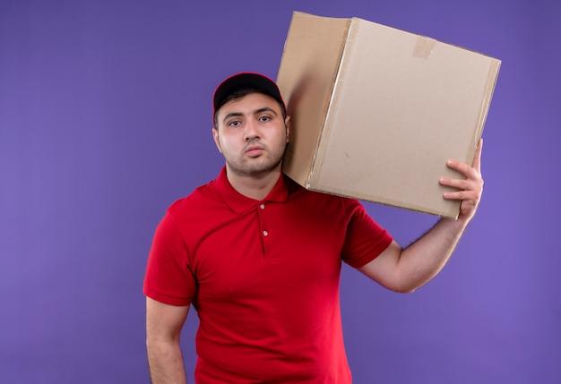 Jonge bezorger in rood uniform en pet met doos pakket op schouder met zelfverzekerde uitdrukking staande over paarse muur