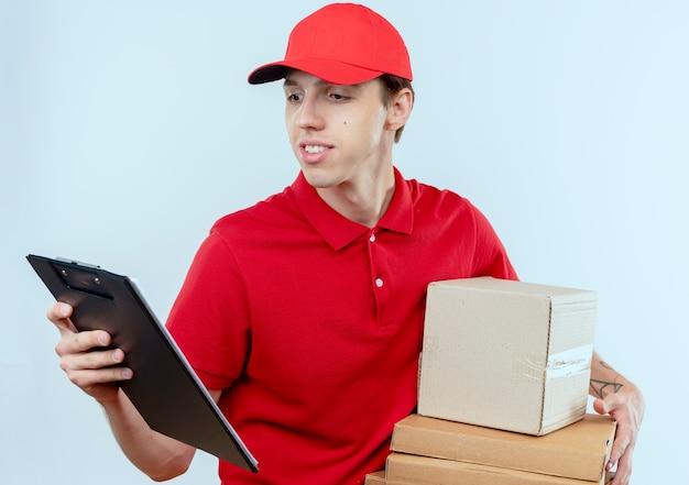 Jonge bezorger in rood uniform en pet met doos pakketten en klembord op zoek zelfverzekerd staande over witte muur