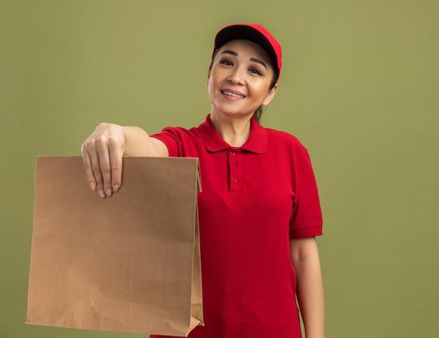 Jonge bezorger in rood uniform en pet met een papieren pakket met een glimlach op het gezicht, blij en positief over de groene muur