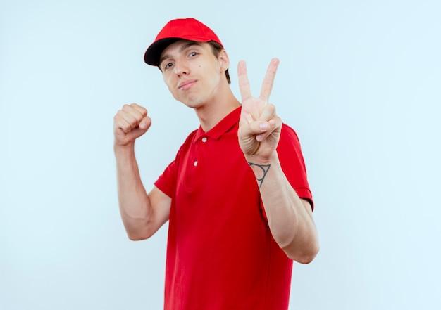 Jonge bezorger in rood uniform en pet met gebalde vuist die overwinningsteken toont dat zelfverzekerd over witte muur kijkt