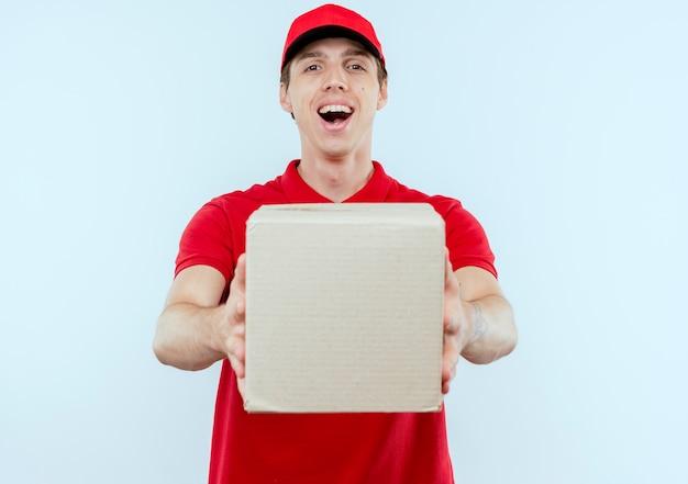 Jonge bezorger in rood uniform en pet met kartonnen doos glimlachend vrolijk blij en positief staande over witte muur