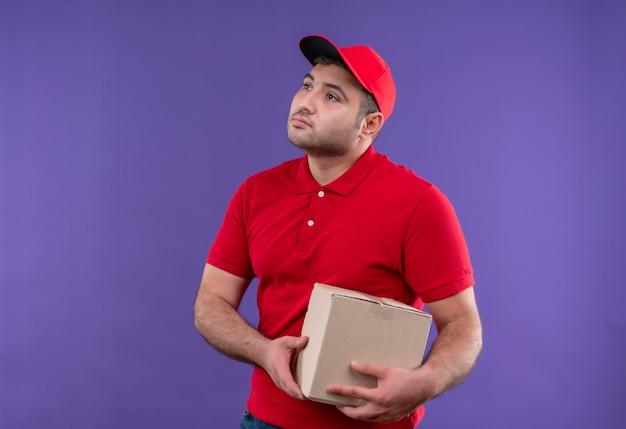 Jonge bezorger in rood uniform en pet met klein pakket opzij kijkend met zelfverzekerde uitdrukking staande over paarse muur