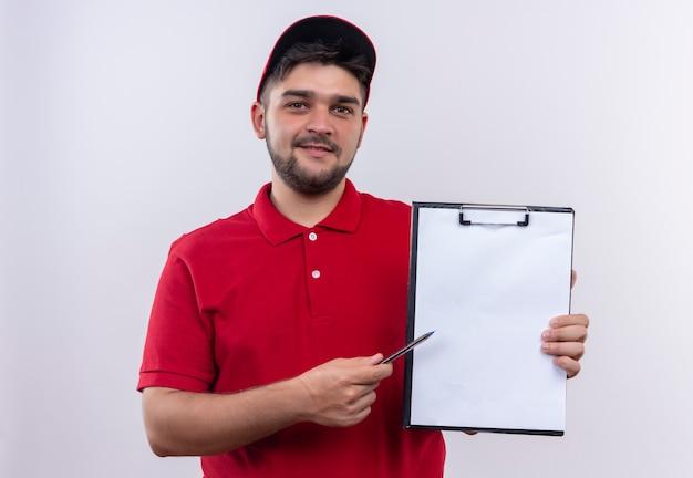 Jonge bezorger in rood uniform en pet met klembord met blanco pagina's die met pen naar het wijzen en vragen om ondertekening